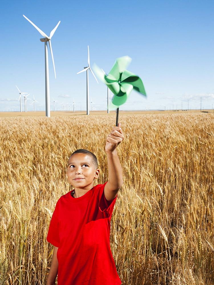 USA, Oregon, Wasco, Girl (10-11) holding fan in wheat field with wind turbines in background