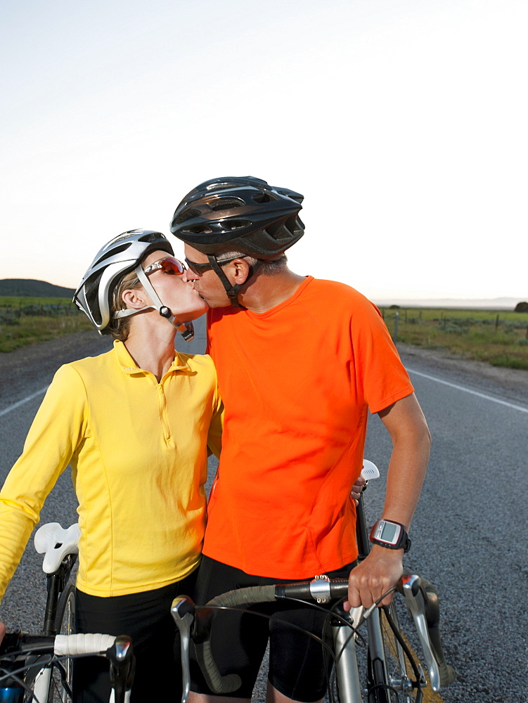 Couple of cyclists kissing on empty road