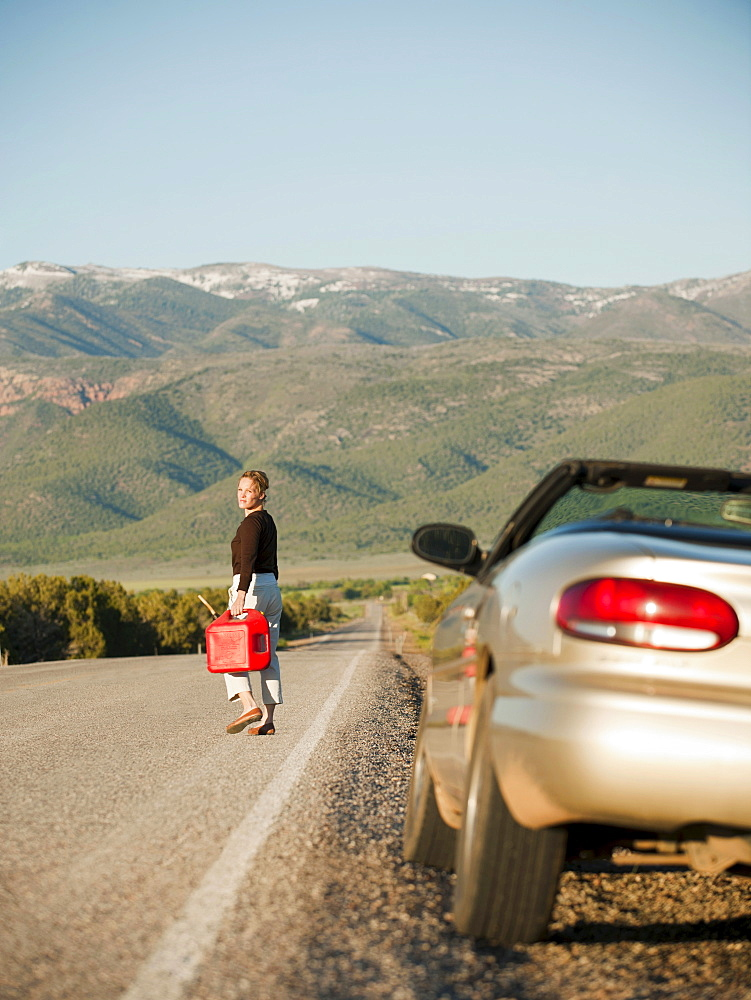 USA, Utah, Kanosh, Woman carrying canister walking along empty road, her car parked on roadside