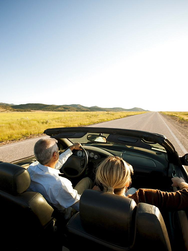 USA, Utah, Kanosh, Mad-adult couple driving through desert plains in convertible car