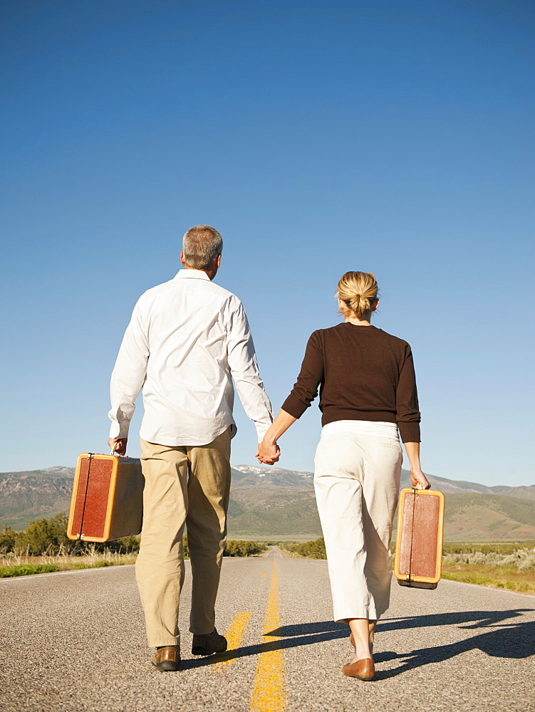 Mid adult couple walking along empty road carrying suitcases