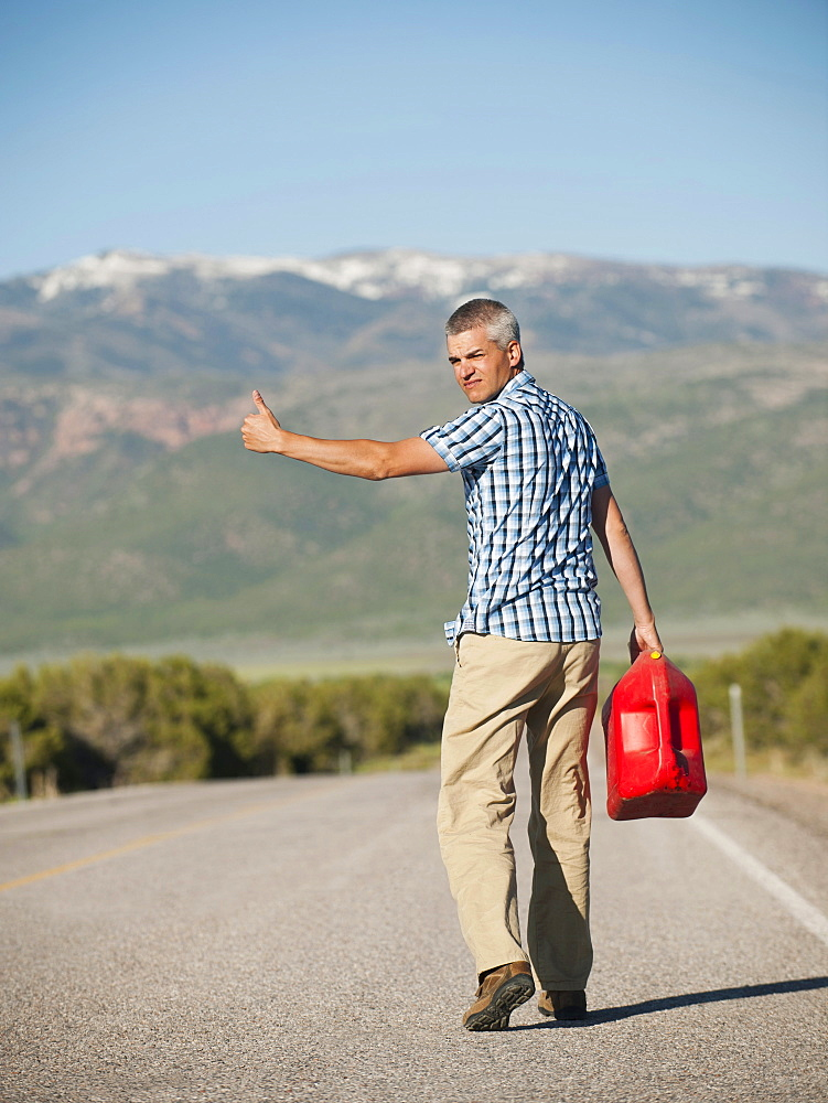 USA, Utah, Kanosh, Mid adult man carrying empty canister attempting to stop vehicles for help