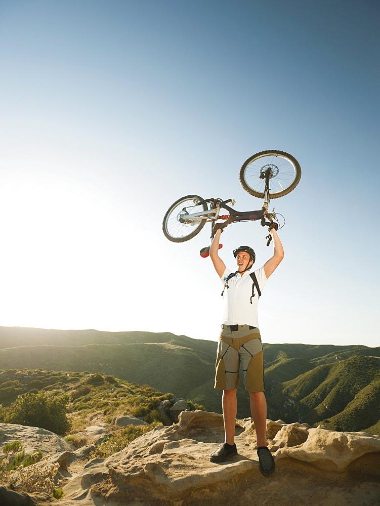 USA, California, Laguna Beach, Mountain biker on top of hill holding up his bike
