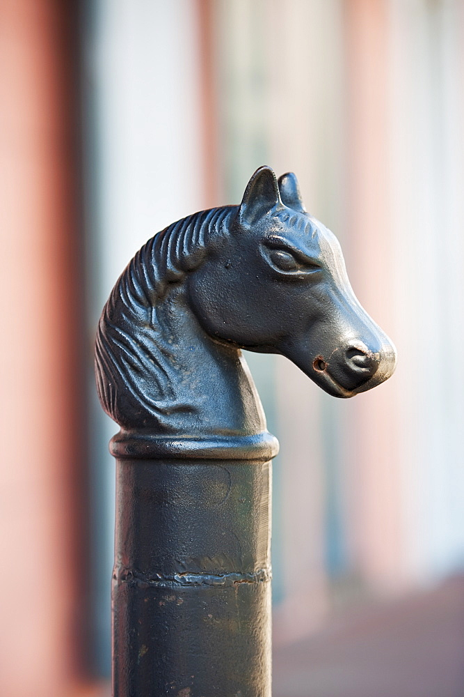 Iron statue of a horse's head on top of a post