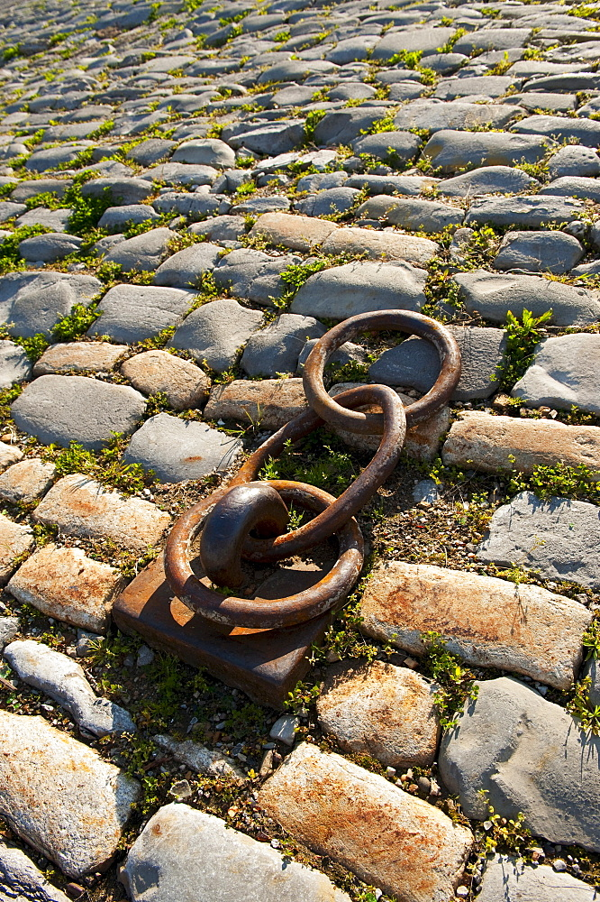 Rusty chain anchored to the ground amongst cobblestones