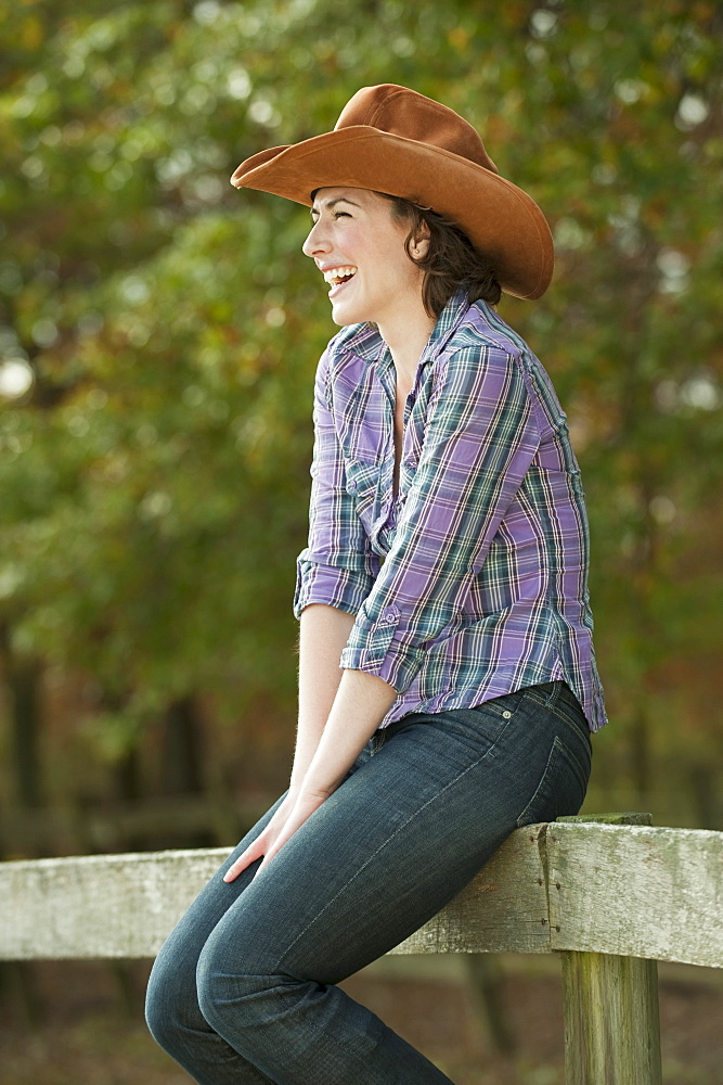Woman sitting on fence