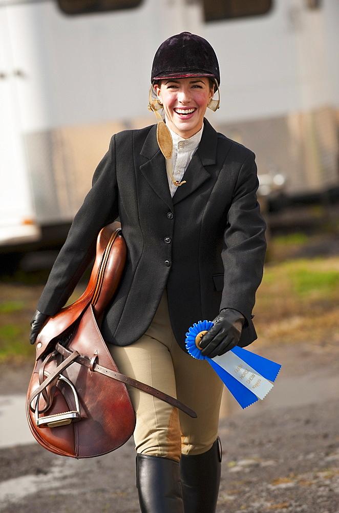 Jockey walking with saddle and ribbon