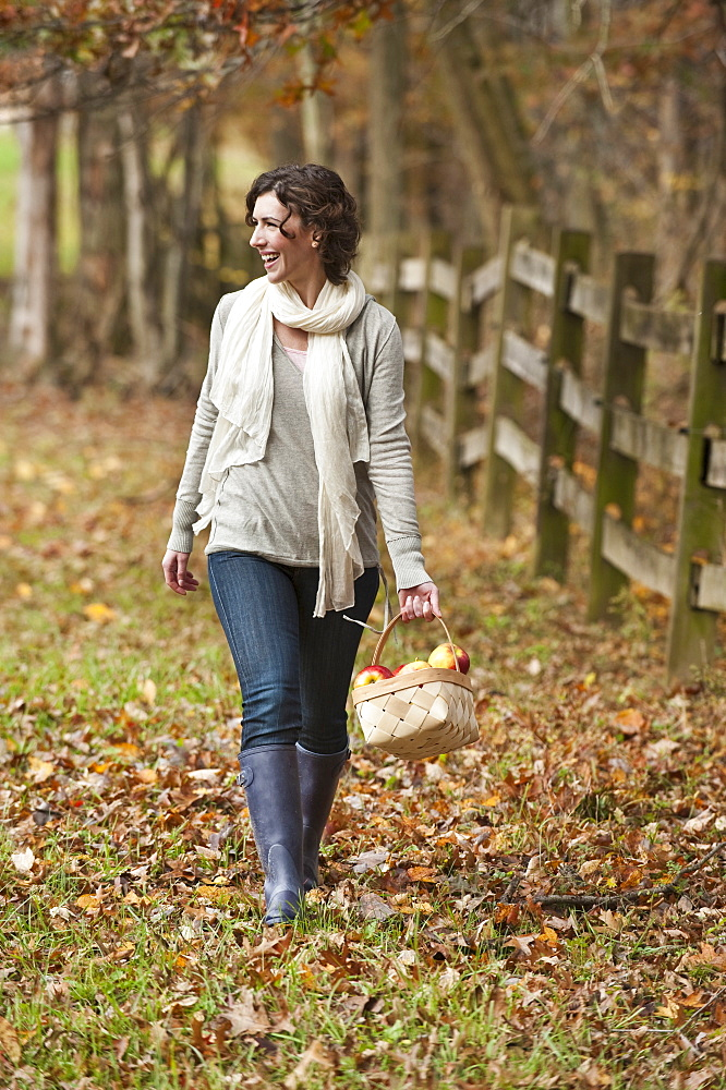 Woman walking with basket of apples