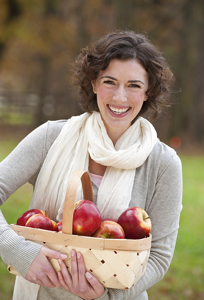 Woman holding basket of apples