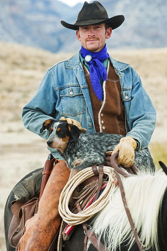 Cowboy and dog on horse