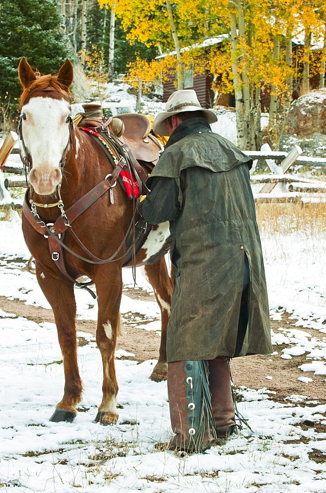 Man putting saddle on horse