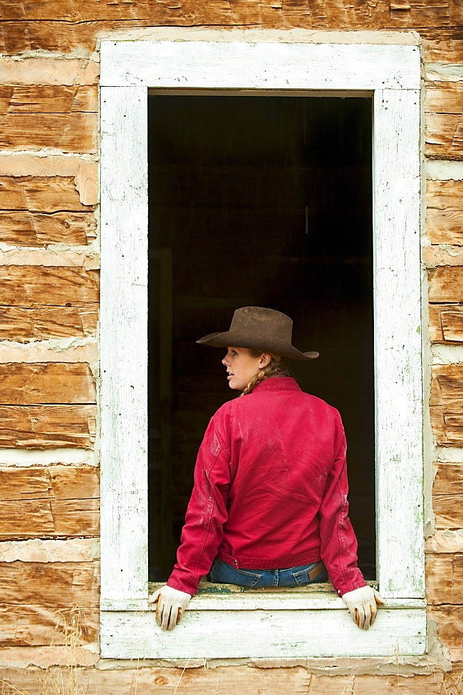 Cowgirl sitting on window ledge