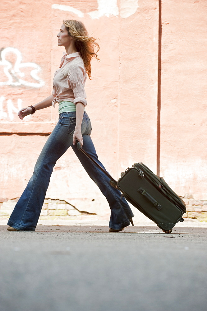A woman walking with a suitcase