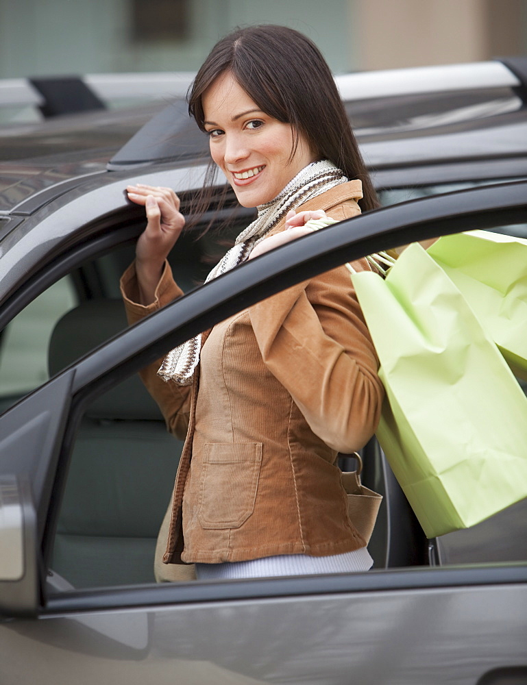 Portrait of woman getting into car with shopping bags
