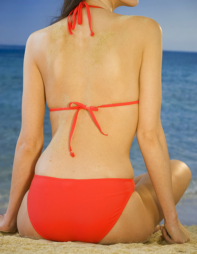 Rear view of woman in bikini sitting on beach, close up