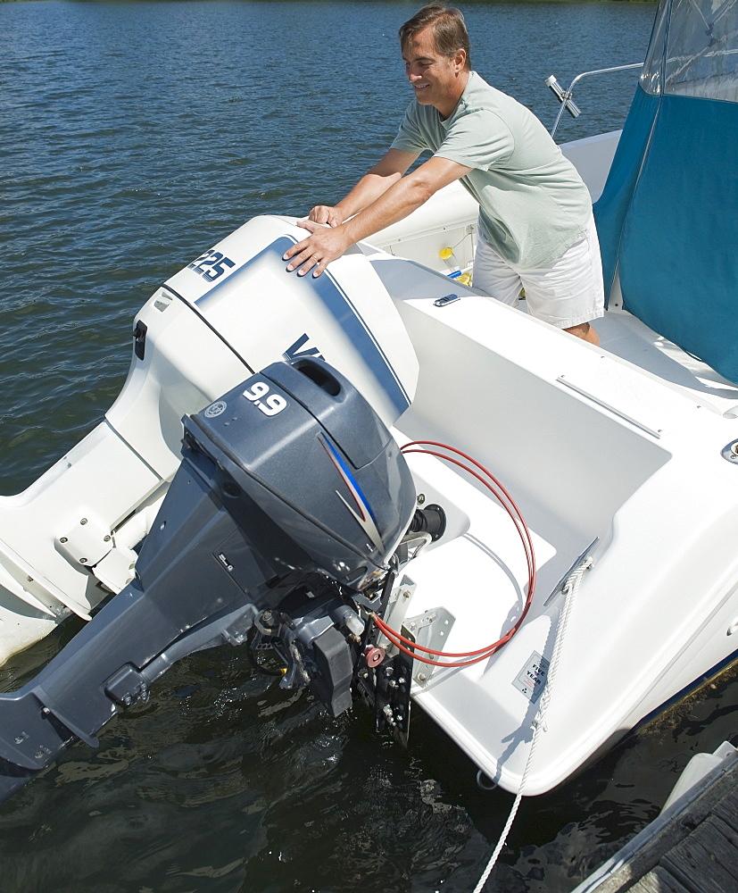 Man adjusting engines on speed boat
