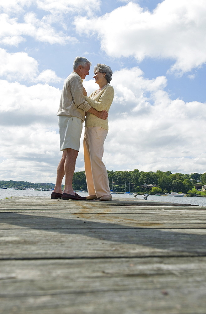 Senior couple hugging on dock