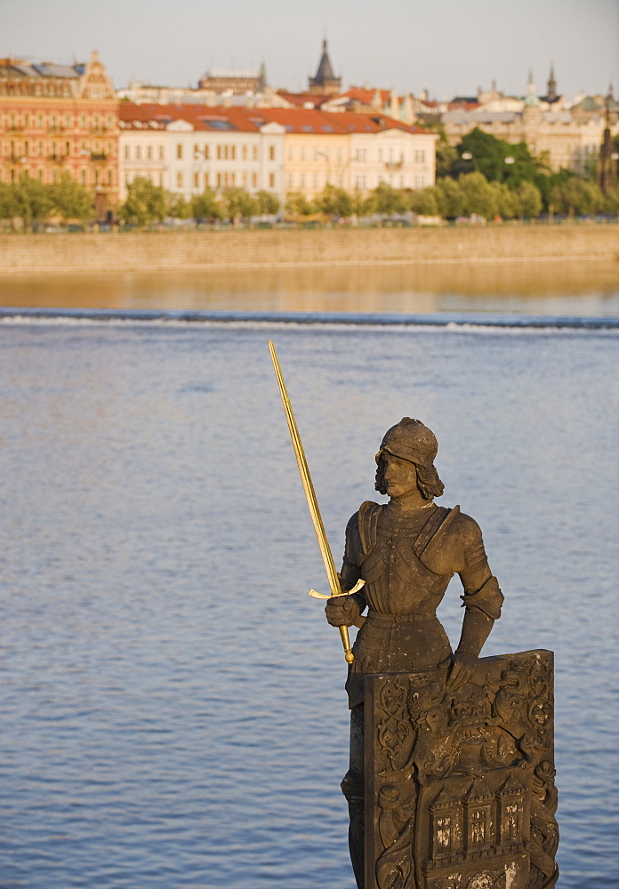 Statue in front of river and city