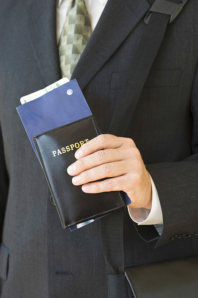 Businessman holding passport and airplane ticket