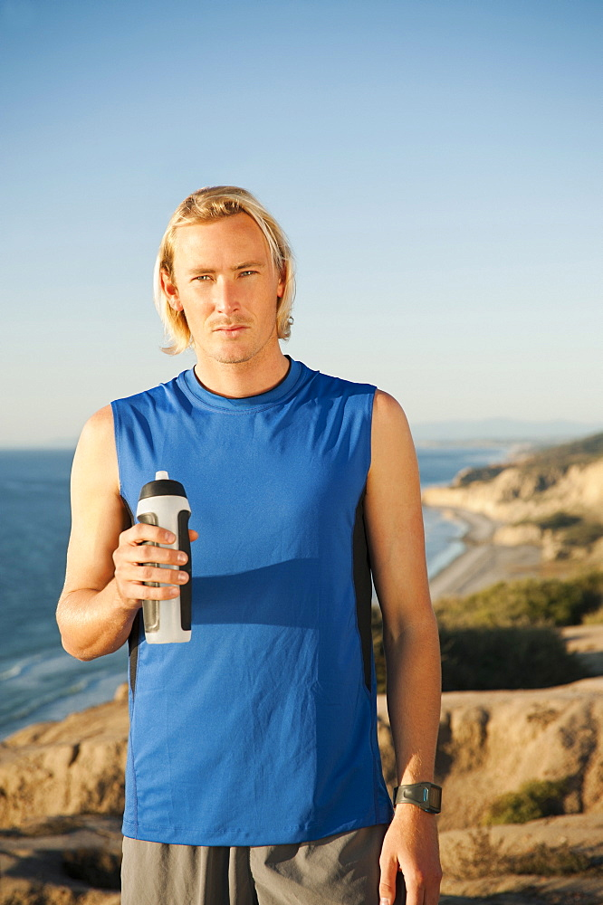 USA, California, San Diego, Portrait of male jogger holding water bottle