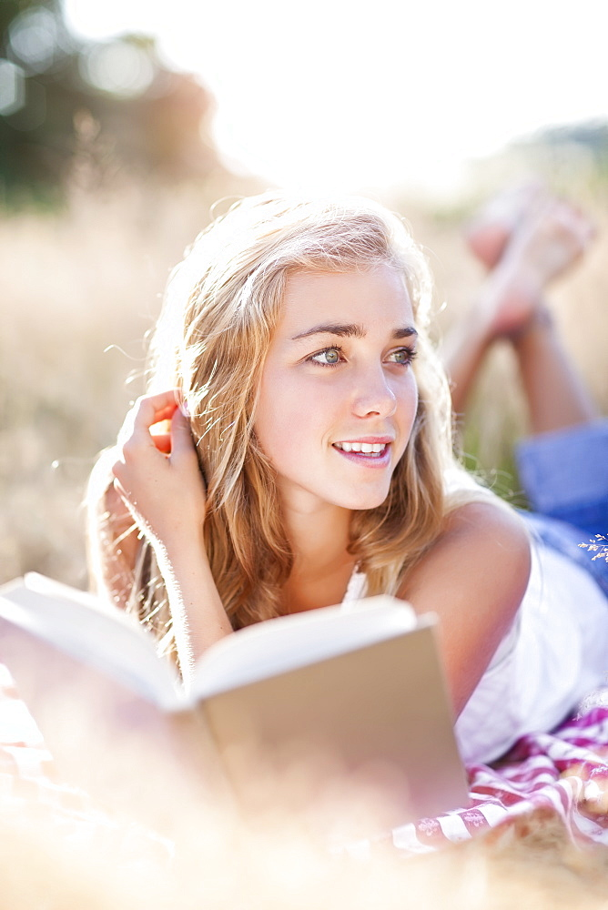 Teenage girl taking break from reading book outdoors