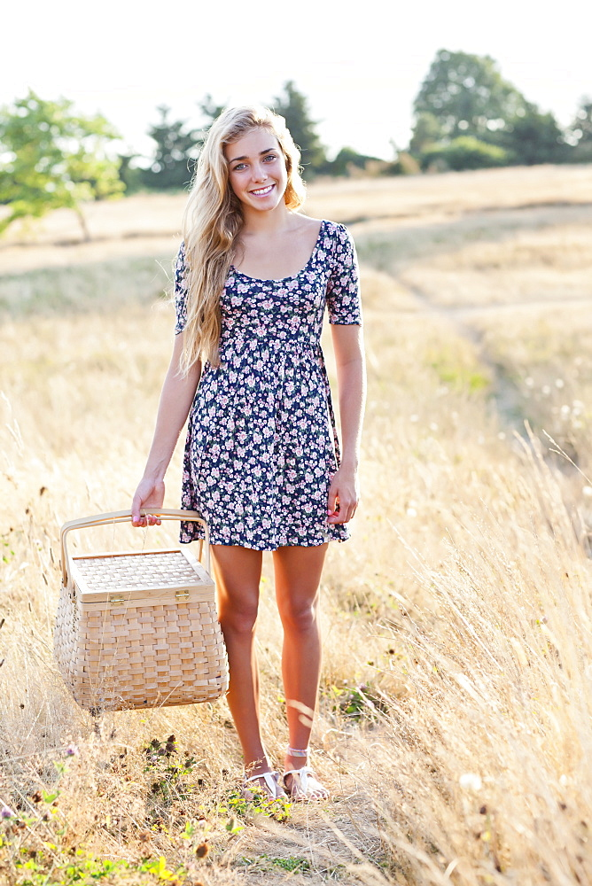 Happy teenage girl (16-17) standing in meadow, holding picnic basket