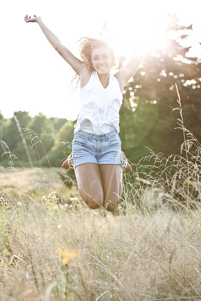 Happy teenage girl (16-17) jumping in bright sunshine
