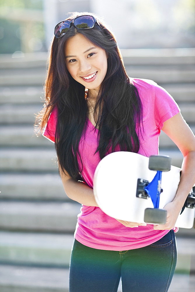Young Asian woman posing with skateboard