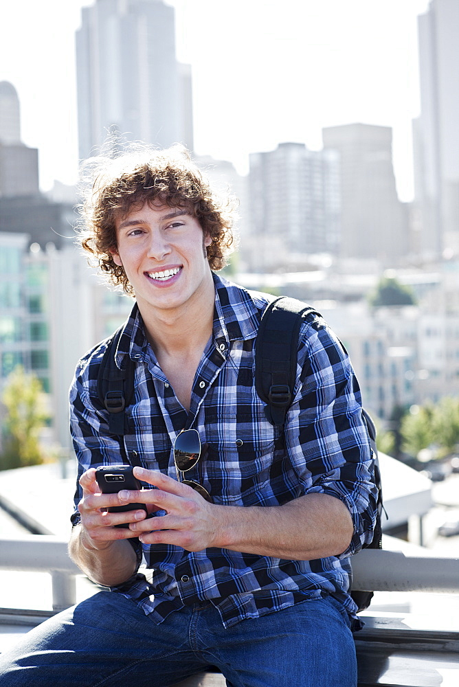 USA, Washington, Seattle, Man text messaging outdoors, skyline in background