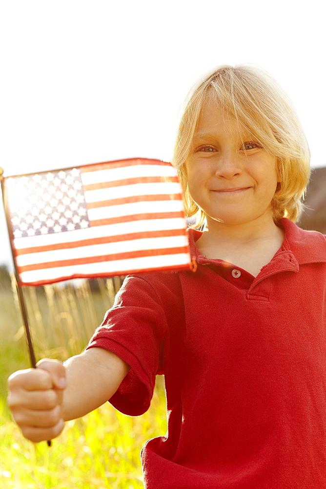 Portrait of boy (6-7) waving American flag in meadow