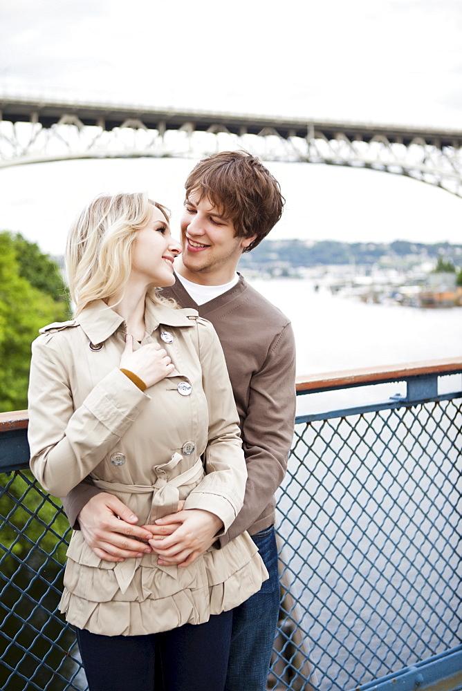 Young couple embracing on bridge