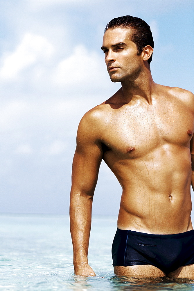 Sexy young man in swim trunks standing in the sea