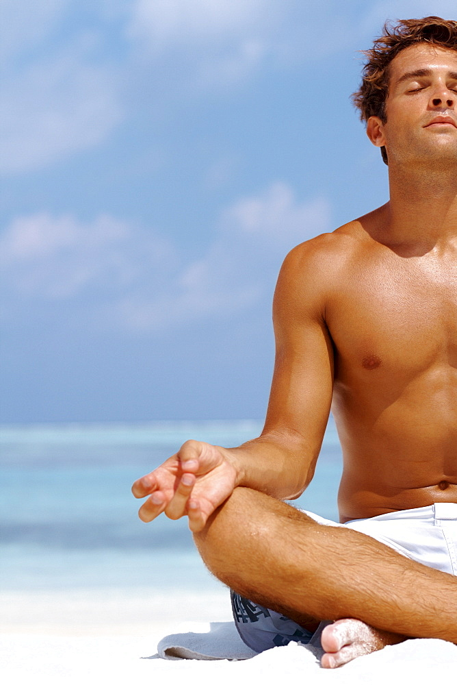 Cropped image of a young man meditating at the beach in a lotus position