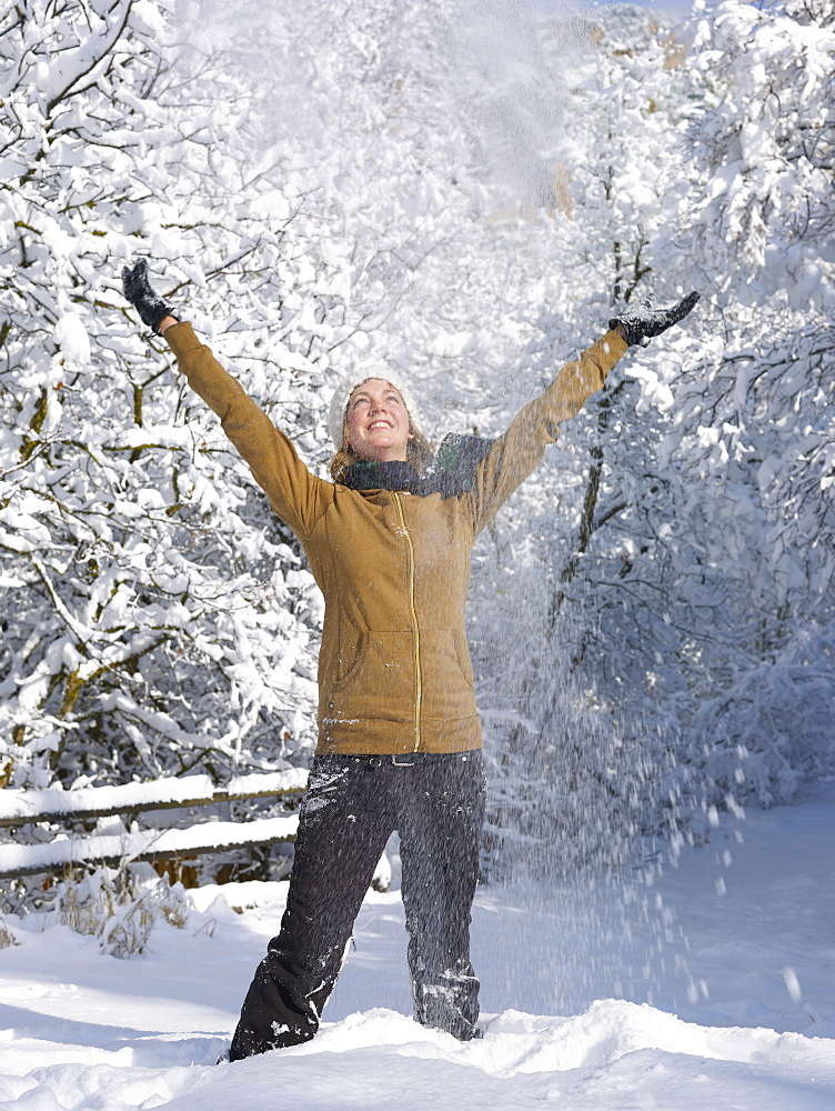 USA, Colorado, young woman throwing snow in air