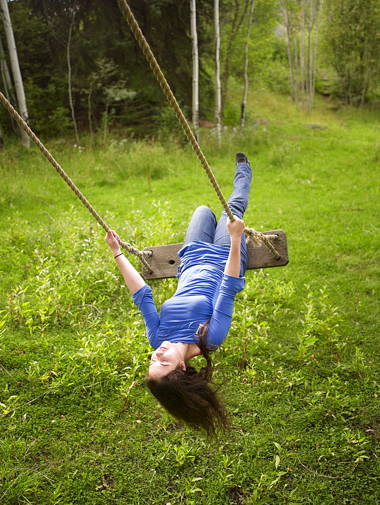 USA, Colorado, Young woman on swing in field