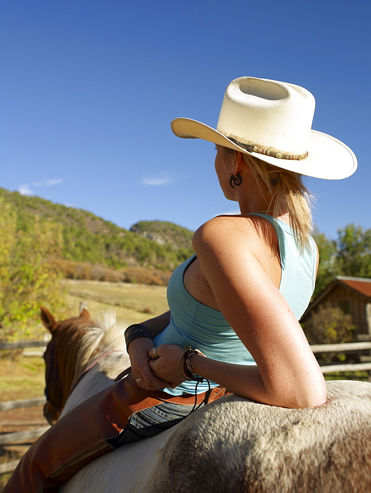 USA, Colorado, Cowgirl relaxing with horse on ranch