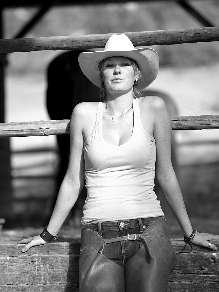 USA, Colorado, Portrait of cowgirl sitting by fence