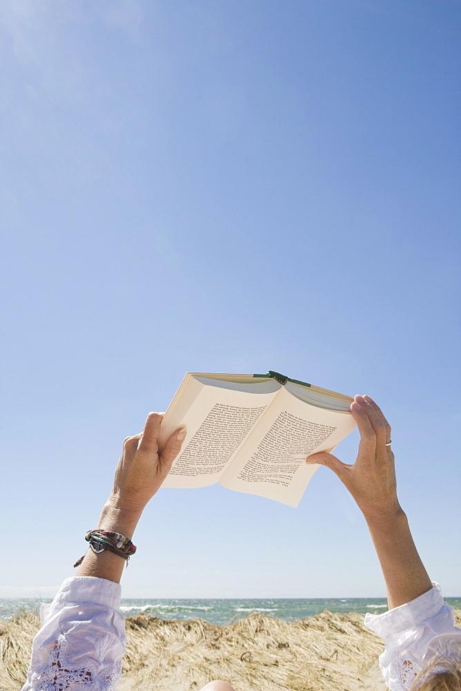 USA, Massachusetts, woman's hands on beach holding book