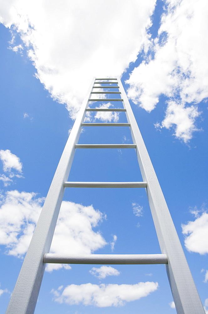 Ladder reaching cloudy sky