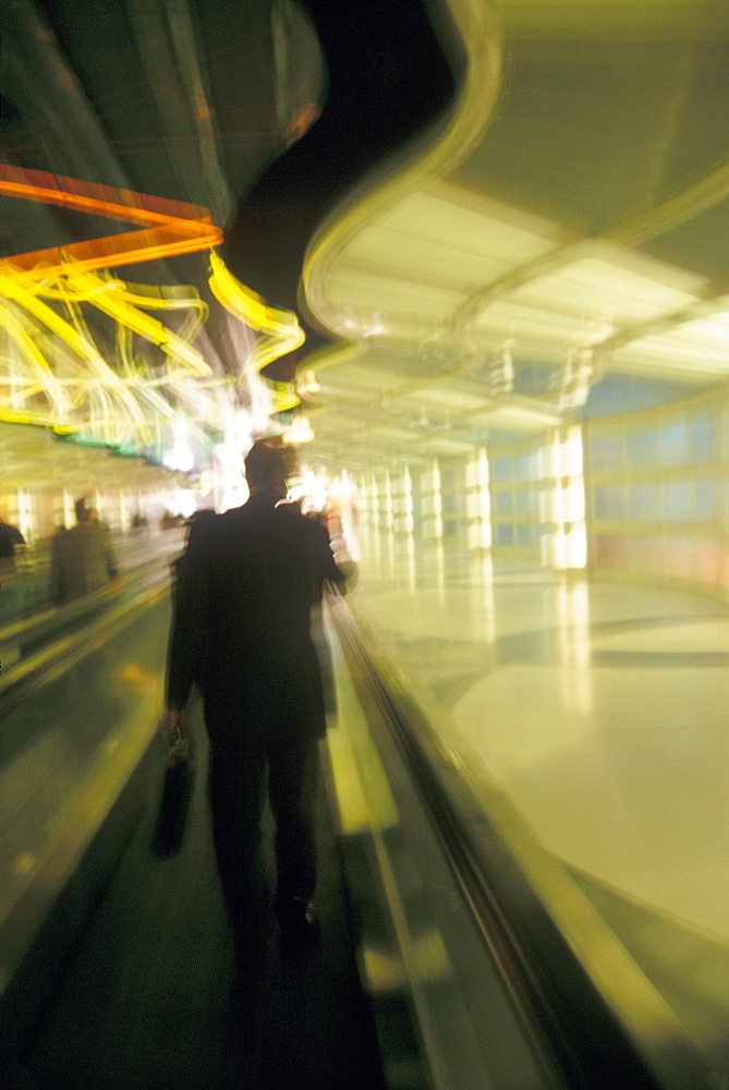 USA, Colorado, Businessman walking through airport, blurred motion