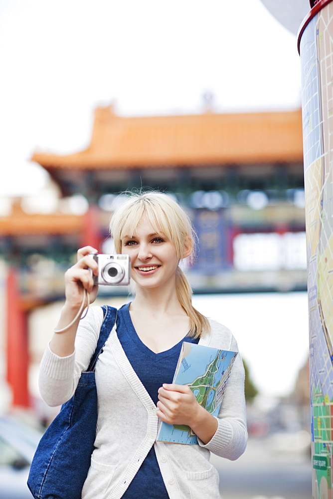 USA, Seattle, Young woman taking photos and holding map