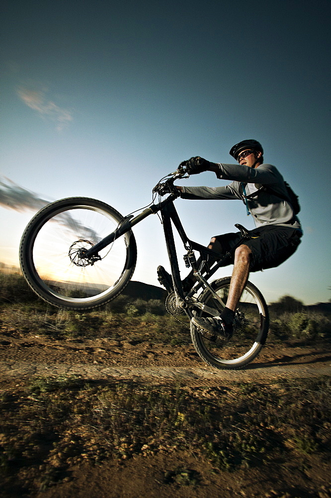Man mountain biking on dirt track