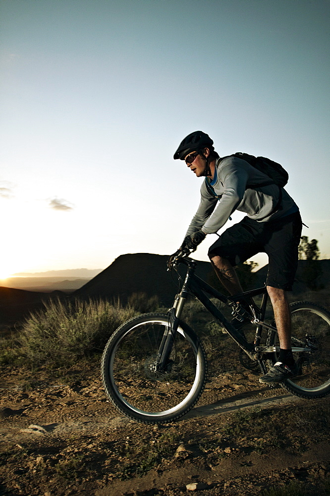 Man mountain biking at sunset