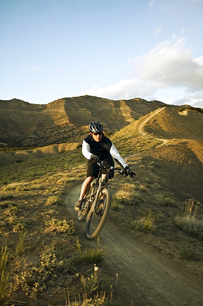 Man mountain biking on mountain track