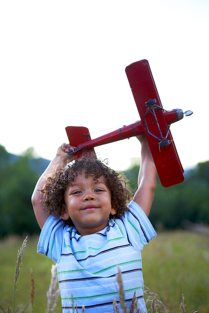 Portrait of boy (2-3) playing with toy aeroplane