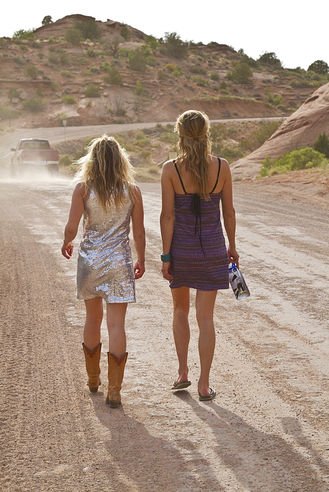 Two young women walking on dirt track in desert