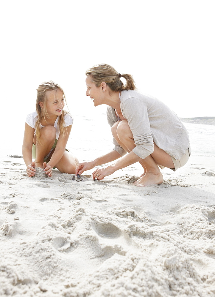 Girl (10-11) playing on beach with mother