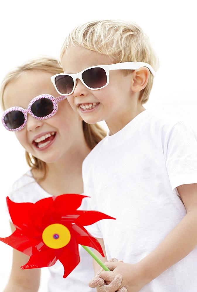 Girl (10-11) and boy (4-5) wearing sunglasses on beach