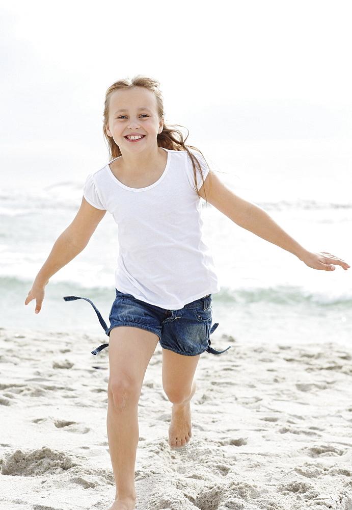 Portrait of girl (10-11) running on beach
