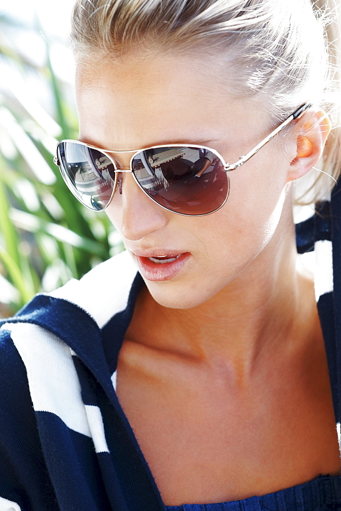 Portrait of young woman wearing striped blouse and sunglasses